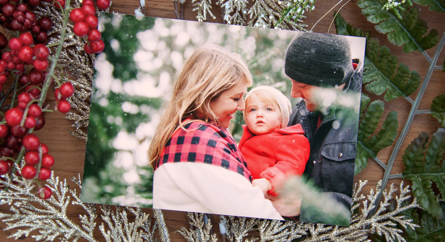 Photo of a couple holding a child in front of holiday decorations